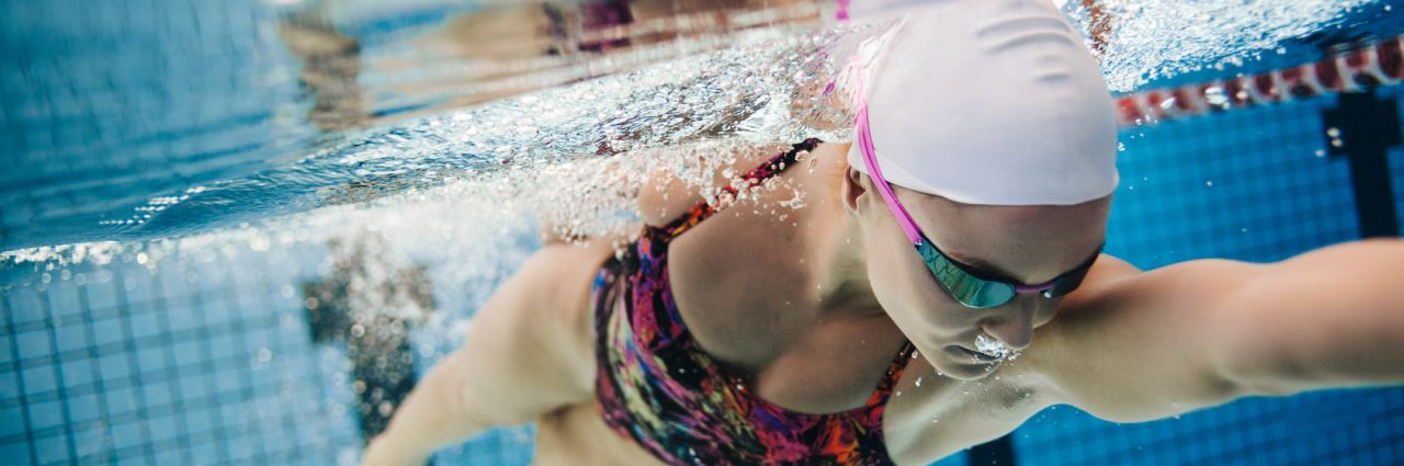 Young female swimmer swimming in pool
